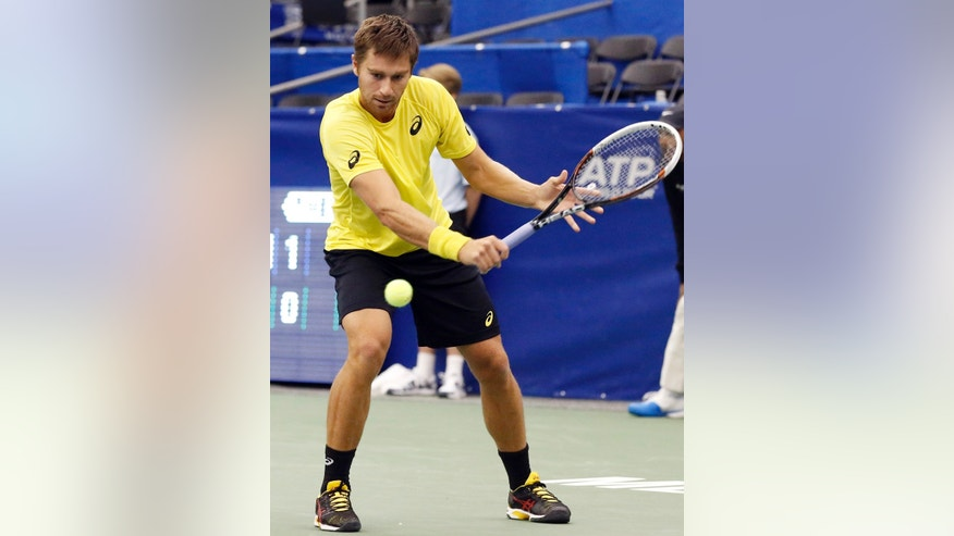 Alex Kuznetsov hits a return to Mikhail Kukushkin of Kazakhstan, during a match at the U.S. National Indoor Tennis  Championships on Thursday, Feb. 13, 2014, in Memphis, Tenn. (AP Photo/Rogelio V. Solis)