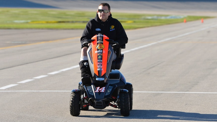 Driver Tony Stewart laughs as he moves from one interview station to another during NASCAR auto racing media day at Daytona International Speedway in Daytona Beach, Fla., Thursday, Feb. 13, 2014. (AP Photo/John Raoux)
