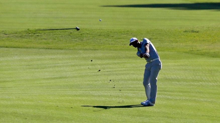 Dustin Johnson makes his approach shot on the ninth fairway in the second round of the Northern Trust Open golf tournament at Riviera Country Club in the Pacific Palisades area of Los Angeles, Friday, Feb. 14, 2014. (AP Photo/Reed Saxon)