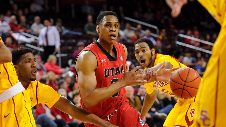 Utah guard Princeton Onwas, center, drives between Southern California guard Kahlil Dukes, right, and teammate guard Pe'Shon Howard (10) during the first half of an NCAA college basketball game, Thursday, Feb. 13, 2014, in Los Angeles. (AP Photo/Gus Ruelas)