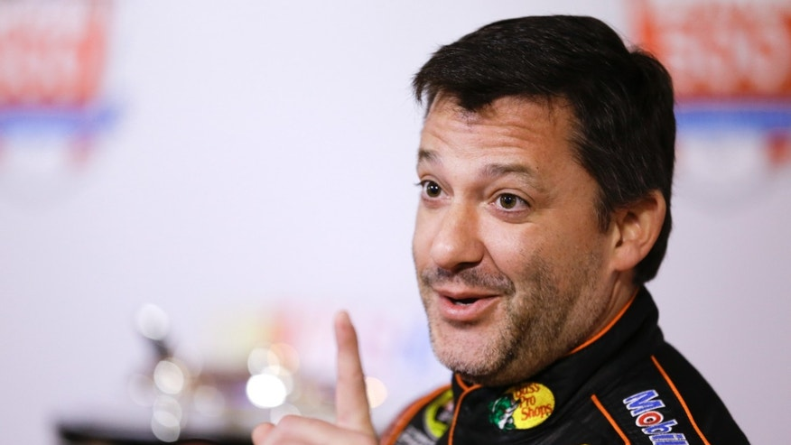 Tony Stewart jokes with members of the media during NASCAR auto racing media day at Daytona International Speedway in Daytona Beach, Fla., Thursday, Feb. 13, 2014. (AP Photo/John Raoux)