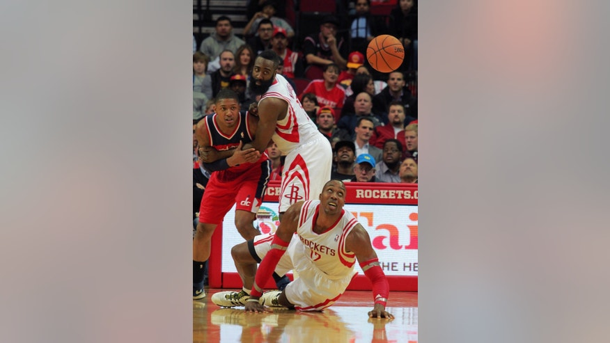 Houston Rockets center Dwight Howard, bottom, watches a loose ball as teammate James Harden, center, holds back Washington Wizards guard Bradley Beal, left, during the second half of an NBA basketball game in Houston, Wednesday, Feb. 12, 2014. (AP Photo/Richard Carson)