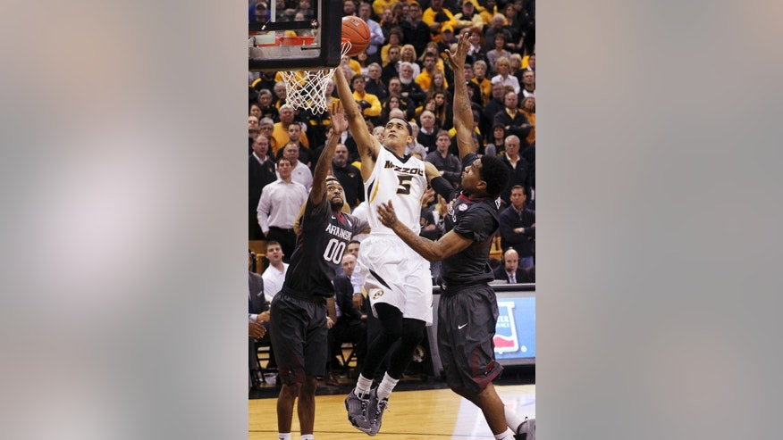 Missouri guard Jordan Clarkson, center, drives to the basket between Arkansas guard Rashad Madden, left, and forward Coty Clarke in second half of an NCAA college basketball game Thursday, Feb. 13, 2014, in Columbia, Mo. (AP Photo/St. Louis Post-Dispatch, Chris Lee)