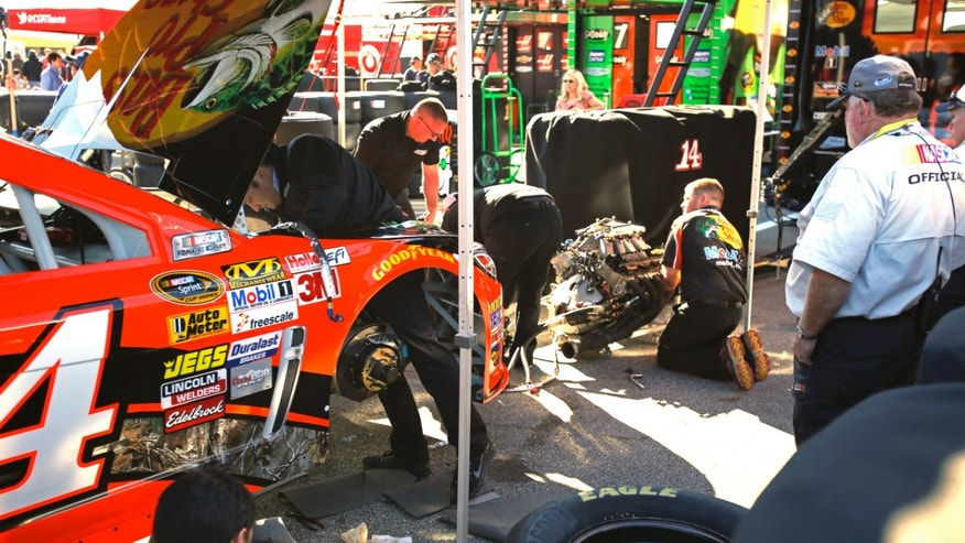 Crew members for driver Tony Stewart work on his car after he had engine problems during a practice for the NASCAR  Daytona 500 auto race at Daytona International Speedway in Daytona Beach, Fla., Saturday, Feb. 15, 2014. (AP Photo/Terry Renna)