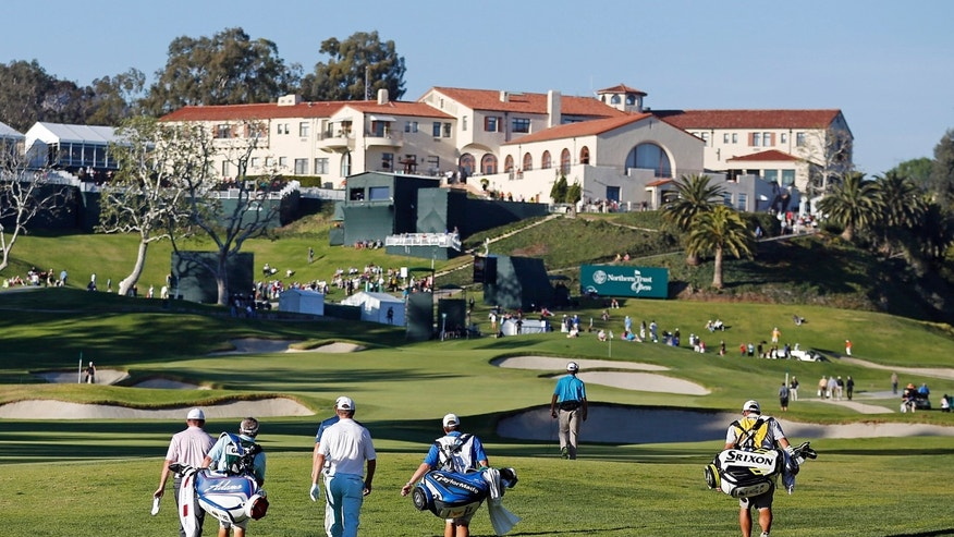 Players walk the ninth fairway during the second round of the Northern Trust Open golf tournament at Riviera Country Club in the Pacific Palisades area of Los Angeles, Friday, Feb. 14, 2014. (AP Photo/Reed Saxon)