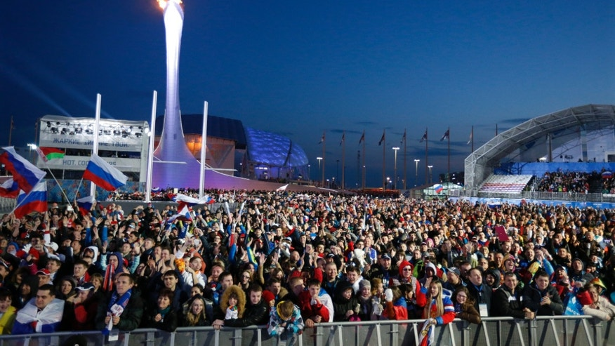 Spectators watch the end of the men's ice hockey game between Russia and the United States on a video screen in the medals plaza at the 2014 Winter Olympics, Saturday, Feb. 15, 2014, in Sochi, Russia. (AP Photo/Tim Donnelly)