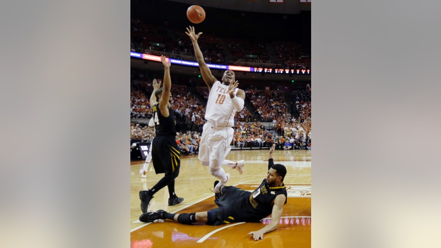 Texas' Jonathan Holmes (10) shoots over a falling West Virginia's Remi Dibo (0) during the first half of an NCAA college basketball game Saturday, Feb. 15, 2014, in Austin, Texas. (AP Photo/Eric Gay)