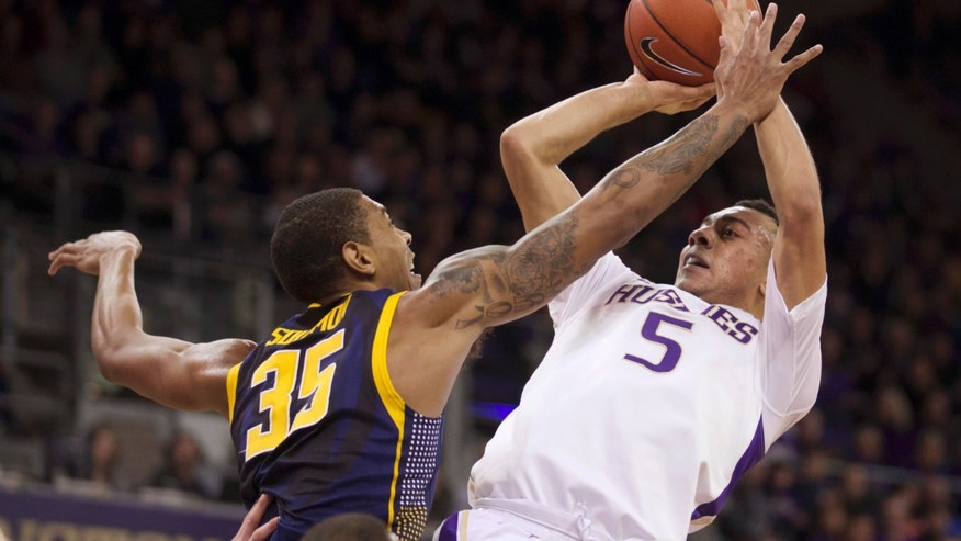 Washington's Nigel Williams-Goss, (5) attempts to shoot over California's Richard Solomon (35) in the first half of an NCAA college basketball game Saturday, Feb. 15, 2014, in Seattle. (AP Photo/Stephen Brashear)