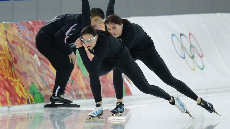 Feb. 15, 2014: Coach Ryan Shimabukuro watches Brittany Bowe of the U.S., front, and Heather Richardson, rear, practice at the Adler Arena Skating Center at the 2014 Winter Olympics in Sochi, Russia.