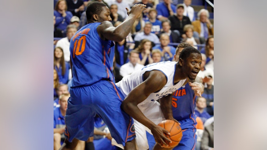 Kentucky's Julius Randle, center, looks for an opening between Florida's Dorian Finney-Smith (10) and Scottie Wilbekin (5) during the first half of an NCAA college basketball game on Saturday, Feb. 15, 2014, in Lexington, Ky. (AP Photo/James Crisp)