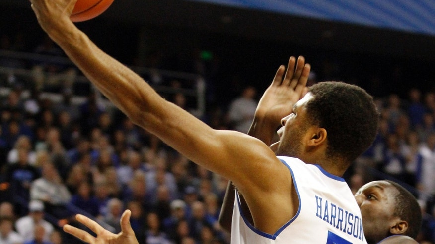 Kentucky's Andrew Harrison (5) shoots under pressure from Florida's Dorian Finney-Smith, right, during the first half of an NCAA college basketball game on Saturday, Feb. 15, 2014, in Lexington, Ky. (AP Photo/James Crisp)