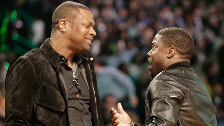 Actor's Chris Tucker, left, and Kevin Hart talk during the skills competition at the NBA All Star basketball game, Saturday, Feb. 15, 2014, in New Orleans. (AP Photo/Gerald Herbert)
