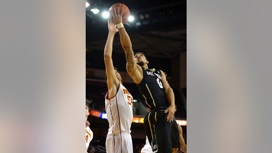 Colorado guard Askia Booker, right, puts up a shot as Southern California center Omar Oraby defends during the first half of an NCAA college basketball game, Sunday, Feb. 16, 2014, Los Angeles. (AP Photo/Mark J. Terrill)