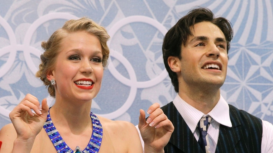 Kaitlyn Weaver and Andrew Poje of Canada wait in the results area after competing in the ice dance short dance figure skating competition at the Iceberg Skating Palace during the 2014 Winter Olympics, Sunday, Feb. 16, 2014, in Sochi, Russia. (AP Photo/Vadim Ghirda)