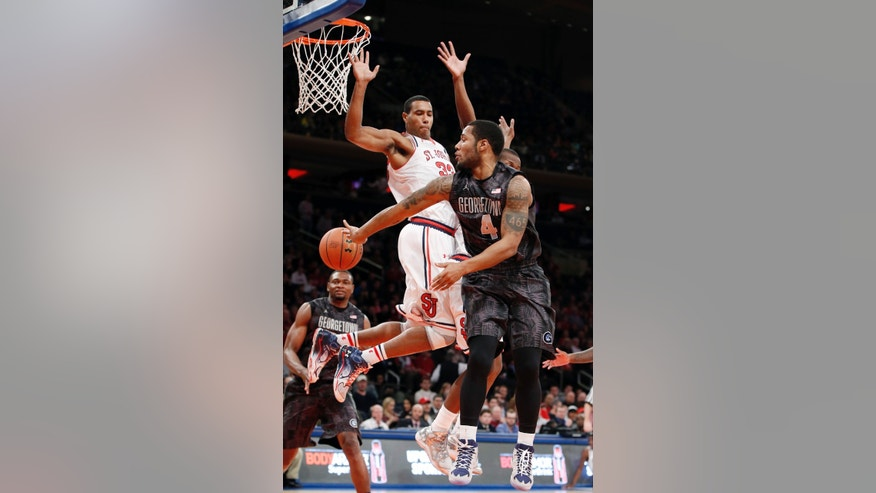 Georgetown guard D'Vauntes Smith-Rivera (4) passes around St. John's forward Orlando Sanchez during the first half of an NCAA college basketball game at Madison Square Garden in New York, Sunday, Feb. 16, 2014. (AP Photo/Kathy Willens)