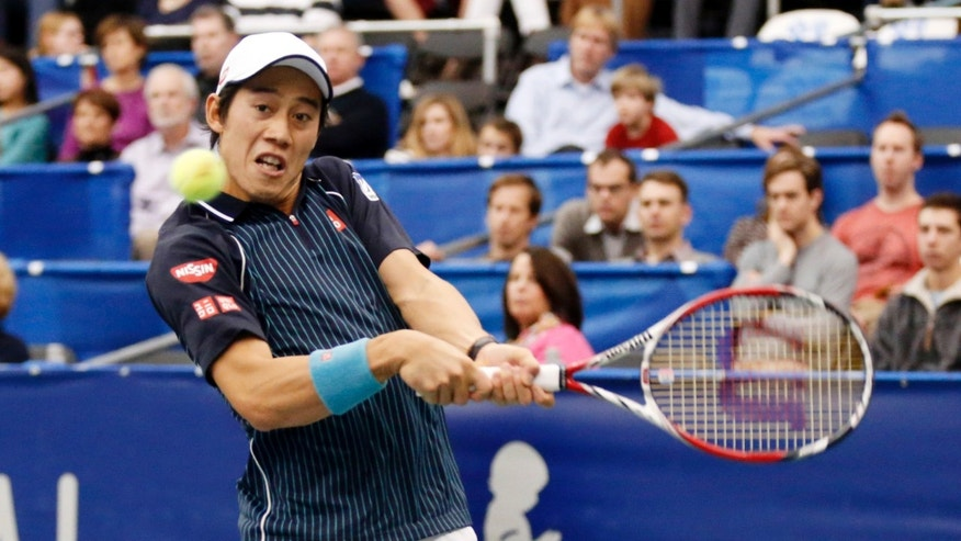 Kei Nishikori, of Japan, hits a return to Ivo Karlovic, of Croatia, in the singles final at the U.S. National Indoor Tennis Championships on Sunday, Feb. 16, 2014, in Memphis, Tenn. (AP Photo/Rogelio V. Solis)