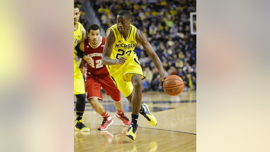 Michigan guard Caris LeVert (23) drives during the first half of an NCAA college basketball game against Wisconsin in Ann Arbor, Mich., Sunday, Feb. 16, 2014. (AP Photo/Carlos Osorio)