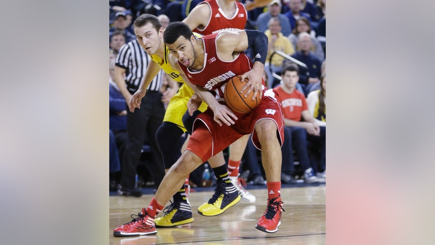 Michigan guard Nik Stauskas, left, reaches in on Wisconsin guard Traevon Jackson (12) during the second half of an NCAA college basketball game in Ann Arbor, Mich., Sunday, Feb. 16, 2014. Wisconsin defeated Michigan 75-62. (AP Photo/Carlos Osorio)