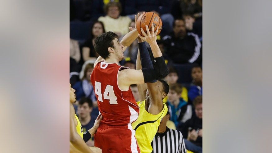 Wisconsin forward Frank Kaminsky (44) shoots over Michigan forward Glenn Robinson III during the first half of an NCAA college basketball game in Ann Arbor, Mich., Sunday, Feb. 16, 2014. (AP Photo/Carlos Osorio)