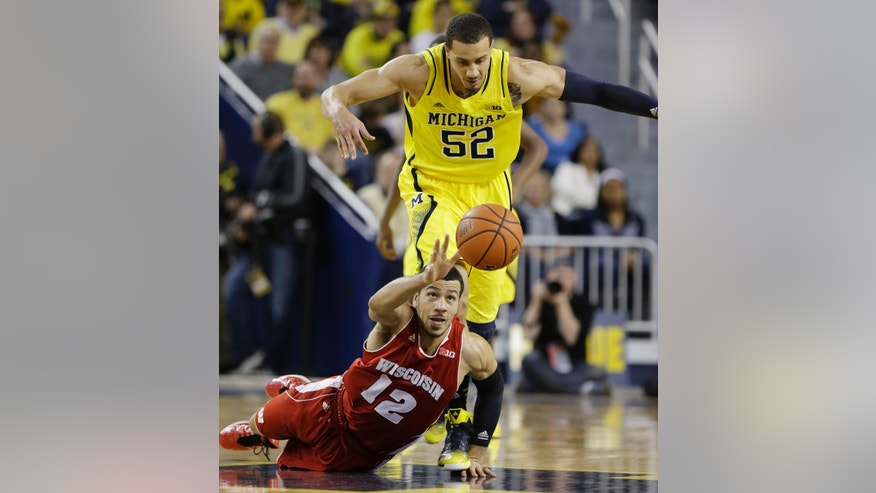 Wisconsin guard Traevon Jackson (12) reaches for the loose ball as Michigan forward Jordan Morgan (52) closes in during the first half of an NCAA college basketball game in Ann Arbor, Mich., Sunday, Feb. 16, 2014. (AP Photo/Carlos Osorio)