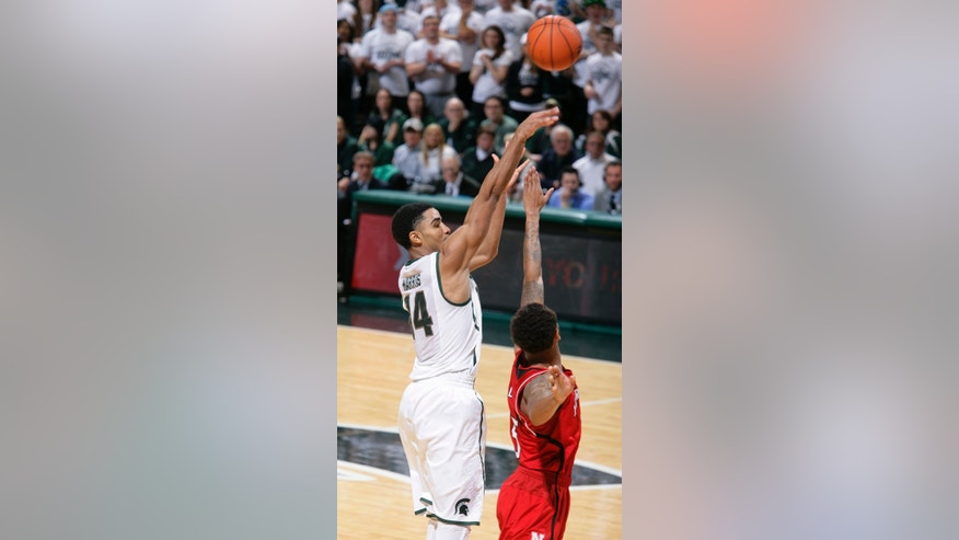 Michigan State's Gary Harris (14) shoots against Nebraska's Ray Gallegos during the first half of an NCAA college basketball game on Sunday, Feb. 16, 2014, in East Lansing, Mich. (AP Photo/Al Goldis)