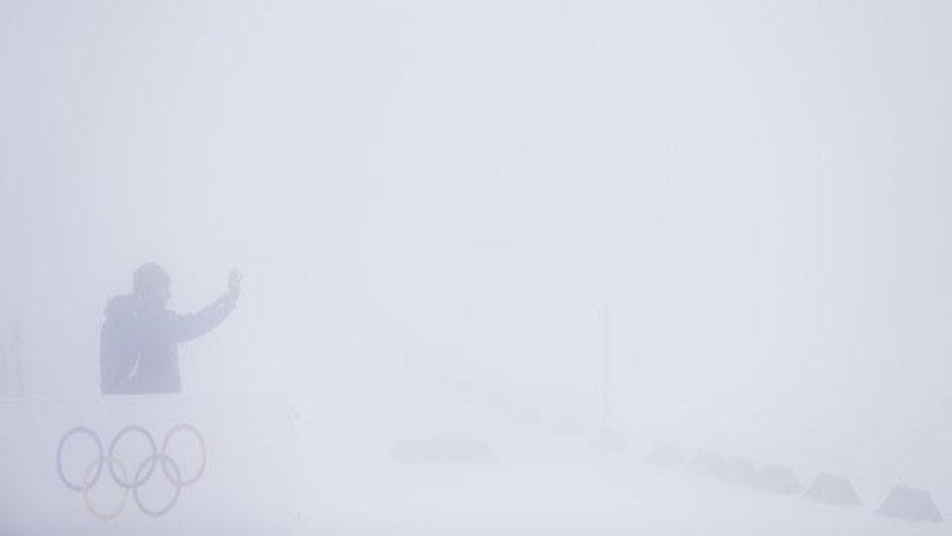 February 17, 2014: A worker gestures as he talks to his colleague in thick fog at Laura Biathlon Centre at the 2014 Winter Olympics in Krasnaya Polyana, Russia. The men's 15-kilometer mass-start biathlon race at the Sochi Olympics has been delayed due to fog, one day after the event had been called off for the same reason. (AP Photo/Felipe Dana)