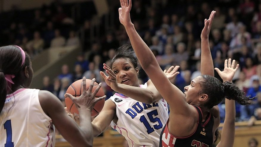 Duke's Richa Jackson (15) passes to teammate Elizabeth Williams (1) while defended by Maryland's Alyssa Thomas (25) during the first half of an NCAA college basketball game in Durham, N.C., Monday, Feb. 17, 2014. (AP Photo/Ted Richardson)