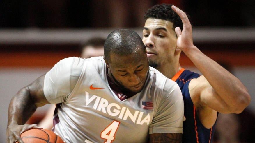 Virginia Tech's Cadarian Raines (4) bumps Virginia's Anthony Gill during the first half of an NCAA college basketball game in Blacksburg, Va., Tuesday, Feb. 18 2014. (AP Photo/The Roanoke Times, Matt Gentry)
