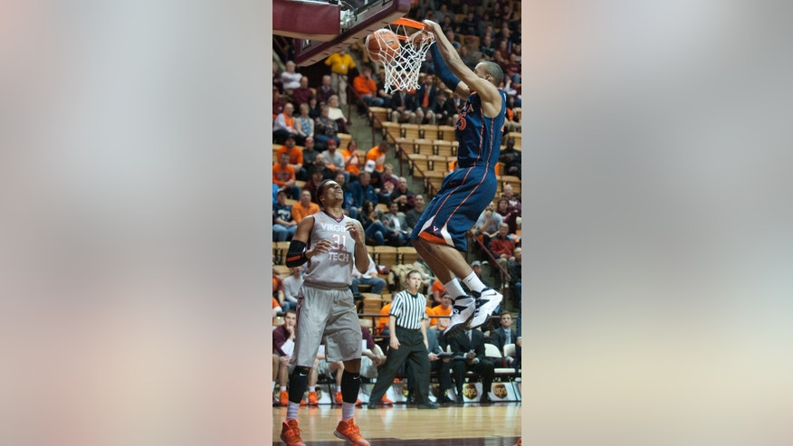 Virginia's Akil Mitchell dunks against Virginia Tech's Jarrell Eddie during the first half of an NCAA college basketball game Tuesday, Feb. 18, 2014, in Blacksburg, Va. (AP Photo/Don Petersen)