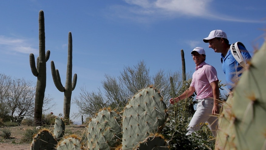 CORRECTS NAME OF CADDIE TO JP FITZGERALD, INSTEAD OF DAVE RENWICK - Rory McIlroy, left, walks off the 17th tee with his caddie, JP Fitzgerald, during a practice round for the Match Play Championship golf tournament Tuesday, Feb. 18, 2014, in Marana, Ariz. (AP Photo/Chris Carlson)