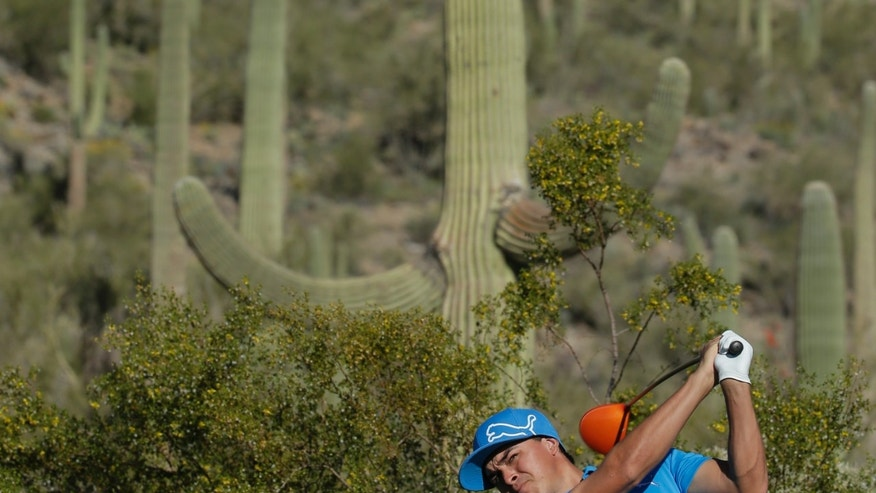 Rickie Fowler watches his tee shot on the 17th hole during a practice round at the Match Play Championship golf tournament on Tuesday, Feb. 18, 2014 in Marana, Ariz. (AP Photo/Chris Carlson)