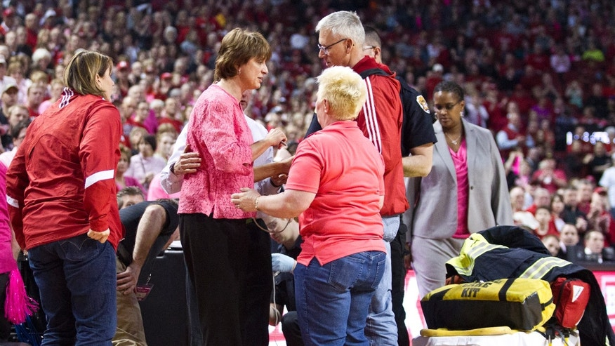 Nebraska head coach Connie Yori, center left, receives help after collapsing on the court during the NCAA women's college basketball game between Nebraska and Indiana at the Pinnacle Bank Arena on Sunday, Feb. 16, 2014, in Lincoln, Neb. (AP Photo/The Journal-Star, Morgan Spiehs) LOCAL TV OUT; KOLN-TV OUT; KGIN-TV OUT; KLKN-TV OUT.