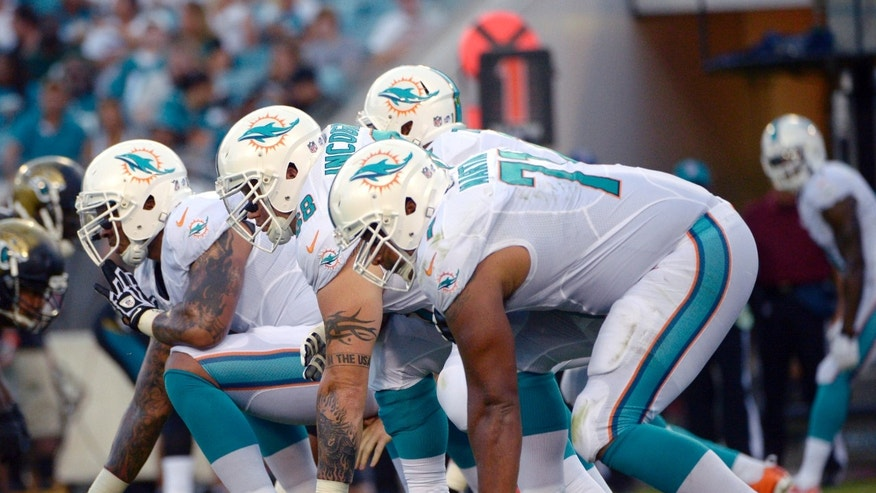"FILE - In this Aug. 9, 2013, file photo, Miami Dolphins center Mike Pouncey, left, guard Richie Incognito (68) and tackle Jonathan Martin (71) set up to block during the first half of an NFL preseason football game against the Jacksonville Jaguars in Jacksonville, Fla. Martin was subjected to ""a pattern of harassment"" that included racist slurs and vicious sexual taunts about his mother and sister by three teammates, according to a report ordered by the NFL.  The report said Incognito, who was suspended by the team in November, and fellow offensive linemen John Jerry and Pouncey harassed Martin.(AP Photo/Phelan M. Ebenhack)"