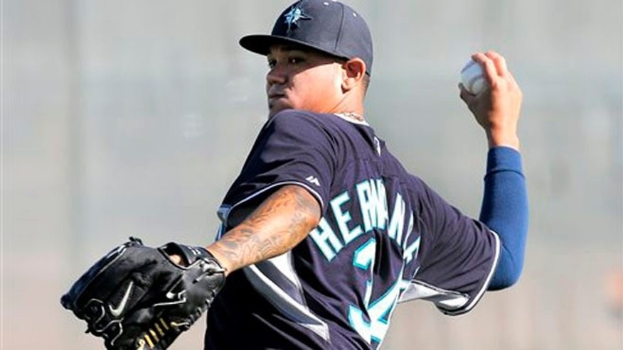 Seattle Mariners pitcher Felix Hernandez throws during their first spring training baseball practice, Thursday, Feb. 13, 2014, in Peoria, Ariz. (AP Photo/Matt York)
