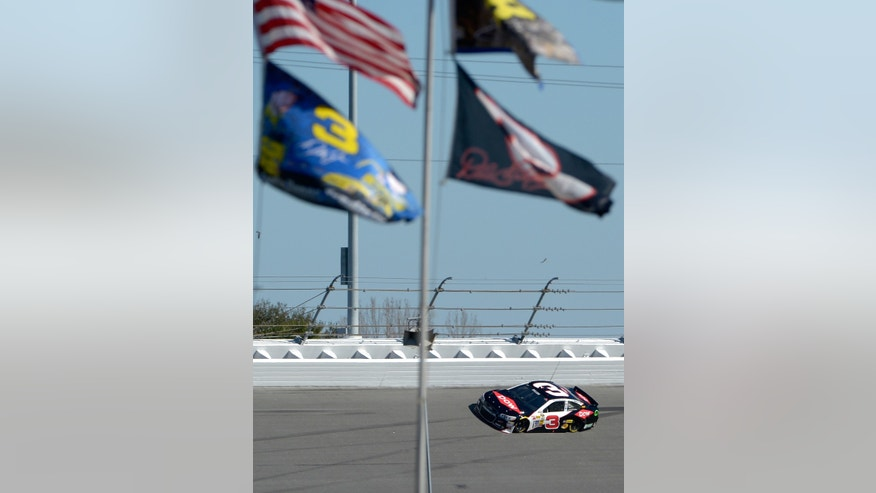 Austin Dillon (3) drives past  No. 3 flags flying in Turn 4 during qualifying for the NASCAR Daytona 500 auto race at Daytona International Speedway in Daytona Beach, Fla., Sunday, Feb. 16, 2014. Dillon won the pole position for the race. (AP Photo/Phelan M. Ebenhack)