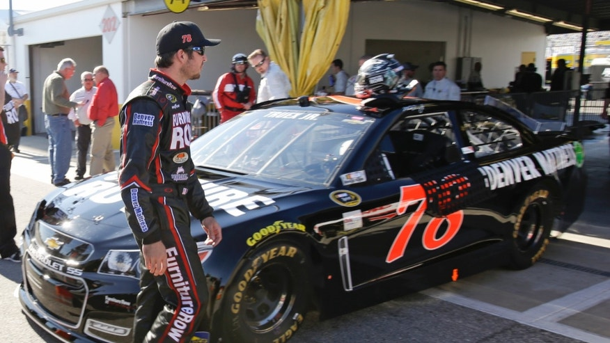 Martin Truex Jr. walks around his car after qualifying in the number two position for the Daytona 500 NASCAR Sprint Cup Series auto race at Daytona International Speedway in Daytona Beach, Fla., Sunday, Feb. 16, 2014. (AP Photo/John Raoux)