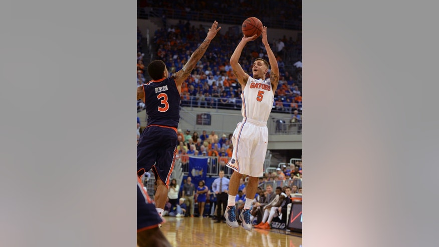 Florida guard Scottie Wilbekin (5) shoots for three points with Auburn guard Chris Denson (3) trying to break up the shot during the first half of an NCAA college basketball game Wednesday Feb. 19, 2014 in Gainesville, Fla. (AP Photo/Phil Sandlin)