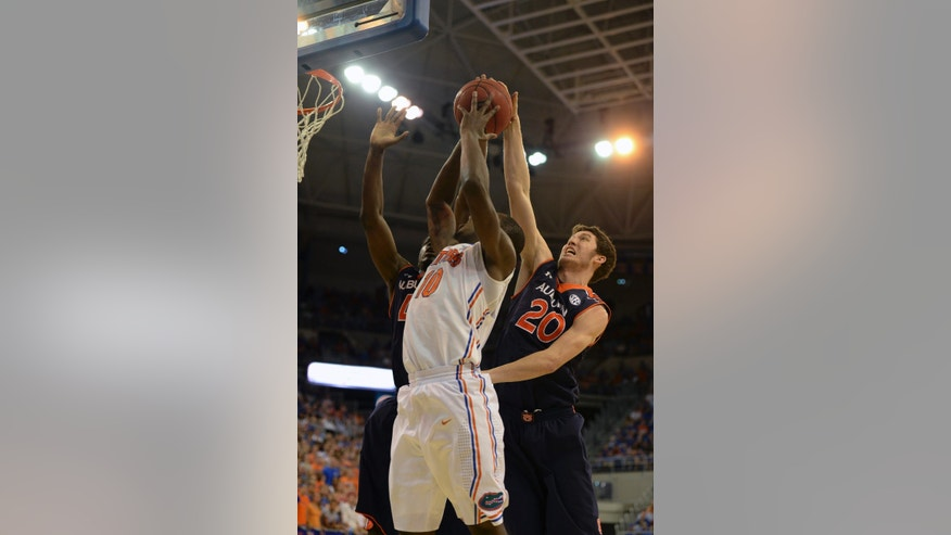 Auburn forward Alex Thompson (20) gets a hand on the ball to keep Florida forward Dorian Finney-Smith (10) from making his shot during the first half of an NCAA college basketball game Wednesday Feb. 19, 2014 in Gainesville, Fla. (AP Photo/Phil Sandlin)