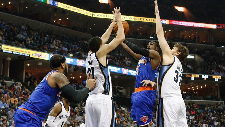 New York Knicks guard Tim Hardaway, Jr. (5) goes to the basket against Memphis Grizzlies forward Tayshaun Prince (21) and center Marc Gasol (33), of Spain, in the first half of an NBA basketball game Tuesday, Feb. 18, 2014, in Memphis, Tenn. (AP Photo/Lance Murphey)