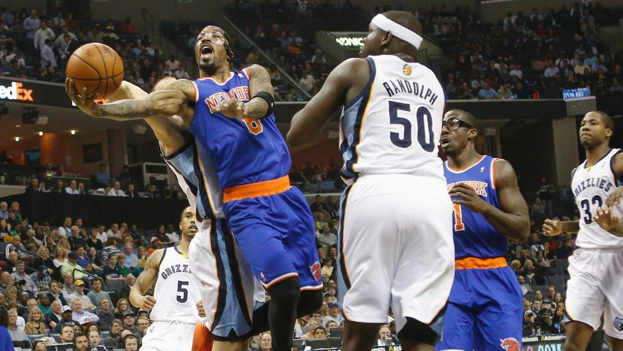New York Knicks guard J.R. Smith (8) drives to the basket against Memphis Grizzlies forward Zach Randolph (50) and Nick Calathes, back, in the first half of an NBA basketball game, Tuesday, Feb. 18, 2014, in Memphis, Tenn. (AP Photo/Lance Murphey)