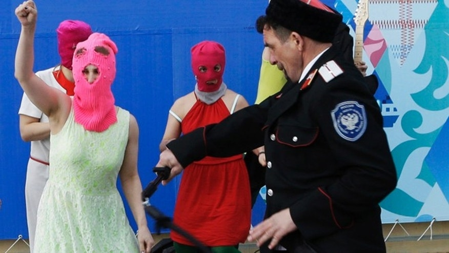 Feb. 19, 2014: Members of the punk group Pussy Riot, including Nadezhda Tolokonnikova in the blue balaclava and Maria Alekhina in the pink balaclava, are attacked by Cossack militia in Sochi, Russia. The group had gathered in a downtown Sochi restaurant, about 21miles from where the Winter Olympics are being held. They ran out of the restaurant wearing brightly colored clothes and ski masks and were set upon by about a dozen Cossacks, who are used by police authorities in Russia to patrol the streets.