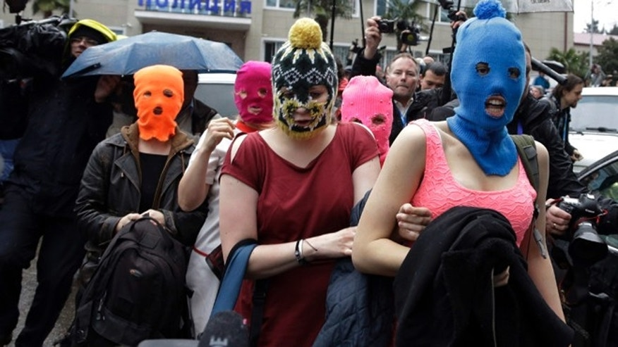 Feb. 18, 2014: Five women wearing balaclavas, two of whom are members of the Russian punk group Pussy Riot, make their way through a crowd after they were released from a police station in Adler, Russia.