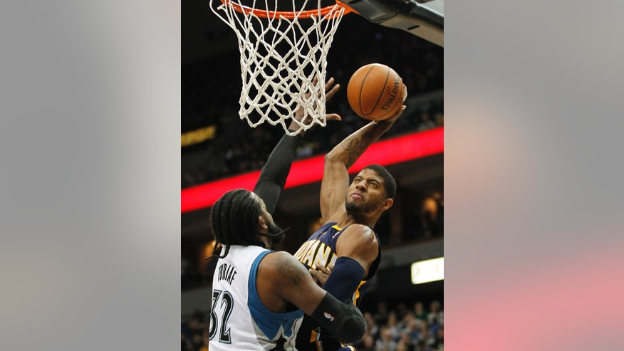 Indiana Pacers forward Paul George, right, goes up against Minnesota Timberwolves, center, Ronny Turiaf (32) during the first half of their NBA basketball game, Wednesday, Feb. 19, 2014 in Minneapolis. (AP Photo/Andy Clayton-King)