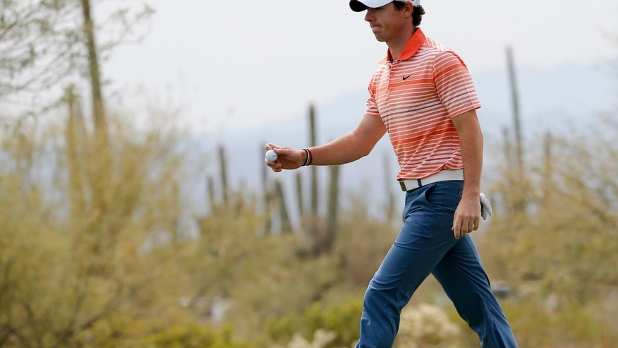Rory McIlroy, of  Northern Ireland, walks off the 10th green in his match against Boo Weekley during the first round of the Match Play Championship golf tournament Wednesday, Feb. 19, 2014, in Marana, Ariz. (AP Photo/Matt York)