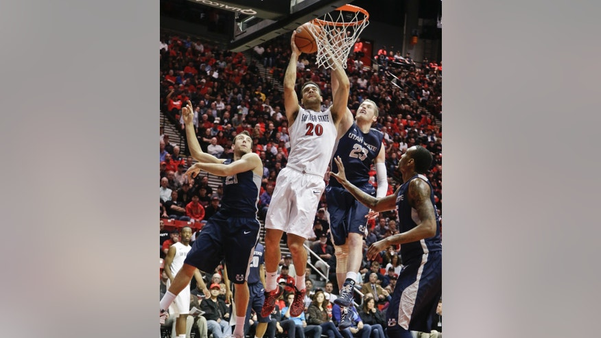 San Diego State forward JJ O'Brien scores despite being surrounded by Utah State 's Spencer Butterfield, left, Kyle Davis, center, and Jarred Shaw during the first half of a NCAA college basketball game Tuesday, Feb. 18, 2014, in San Diego. (AP Photo/Lenny Ignelzi)