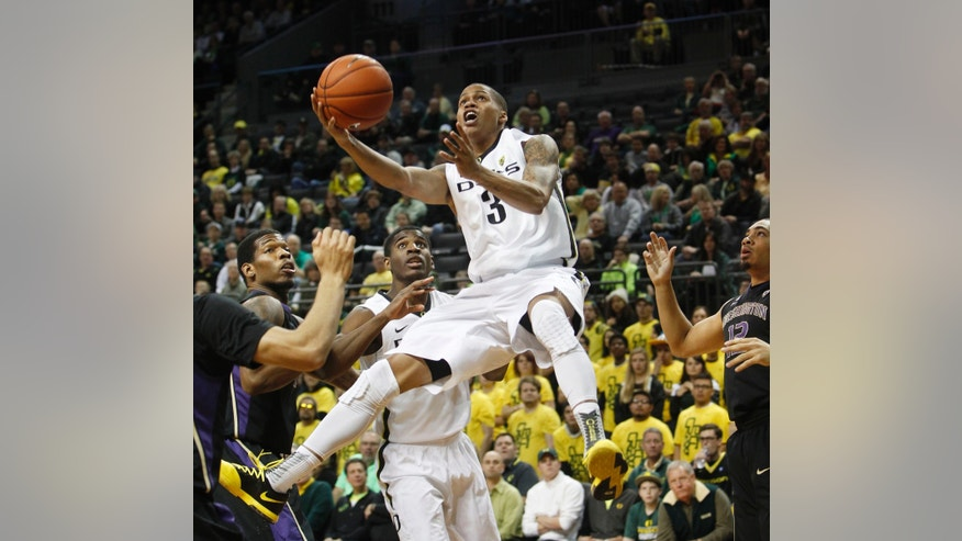 Oregon's Joseph Young goes up for a shot past Washington's C.J. Wilcox, left, Oregon's Damyean Dotson, center left, and Washington's Andrew Andrews during the first half an NCAA college basketball game in Eugene, Ore., on Wednesday, Feb. 19, 2014. (AP Photo/Chris Pietsch)
