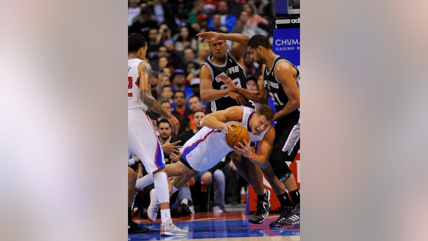 Los Angeles Clippers forward Blake Griffin, bottom middle, dives for the loose ball as San Antonio Spurs forward Boris Diaw (33), of France, and forward Tim Duncan (21) look on in the first half of a NBA basketball game, Tuesday, Feb. 18, 2014, in Los Angeles.(AP Photo/Gus Ruelas)