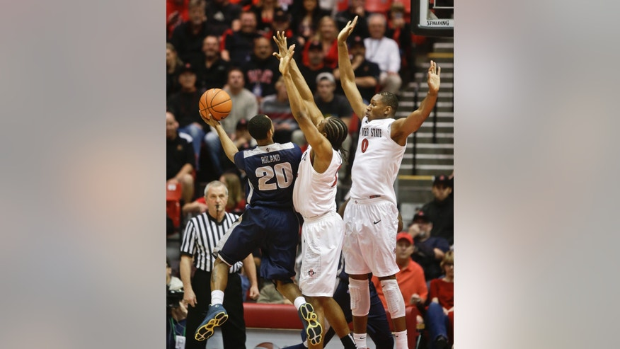 Utah State guard TeNale Roland throwsd up a left handed shot against the tight defense of San Diego State forward Josh Davis and Skylar Spencer, right, during the first half of a NCAA college basketball game  Tuesday, Feb. 18, 2014, (AP Photo/Lenny Ignelzi)