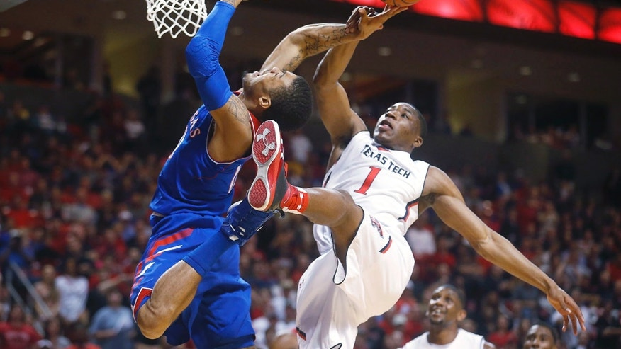 Kansas' Frank Mason (0) is fouled by Texas Tech's Randy Onwuasor (1) during their NCAA college basketball game in Lubbock, Texas, Tuesday, Feb, 18, 2014. (AP Photo/Lubbock Avalanche-Journal, Stephen Spillman)