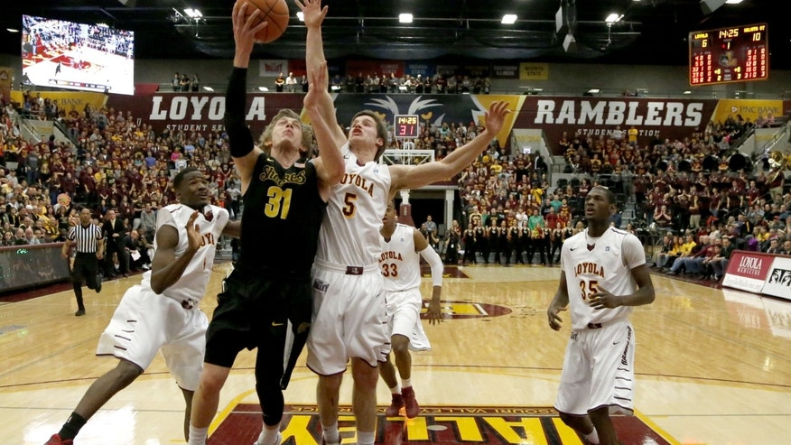 Wichita State guard Ron Baker (31) scores between Loyola of Chicago guard Devon Turk, left, and Joe Crisman (5) during the first half of an NCAA college basketball game Wednesday, Feb. 19, 2014, in Chicago. (AP Photo/Charles Rex Arbogast)